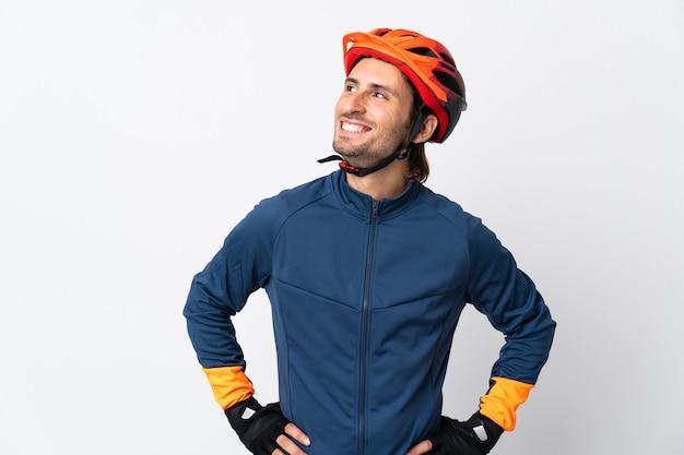 Homem jovem ciclista isolado no branco pensando em uma ideia enquanto olha para cima