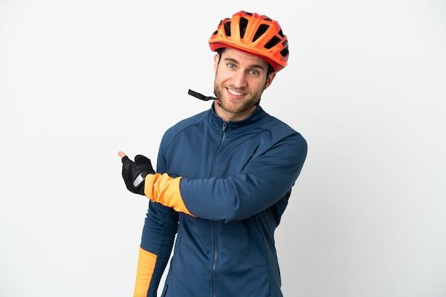 Homem jovem ciclista isolado no fundo branco apontando para trás
