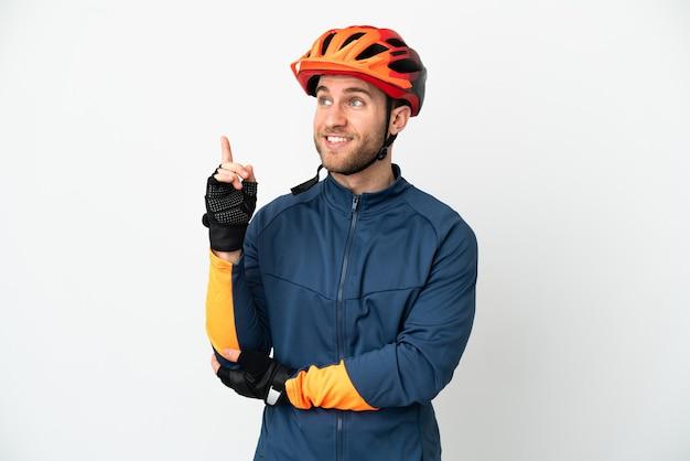 Homem jovem ciclista isolado no fundo branco apontando uma ótima ideia