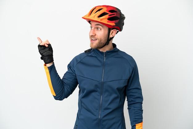 Homem jovem ciclista isolado no fundo branco com a intenção de descobrir a solução enquanto levanta um dedo