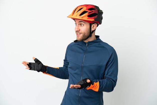 Homem jovem ciclista isolado no fundo branco com expressão de surpresa ao olhar para o lado