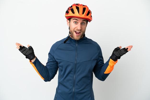 Homem jovem ciclista isolado no fundo branco com expressão facial chocada