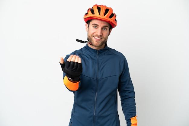 Homem jovem ciclista isolado no fundo branco, convidando para vir com a mão. feliz que você veio