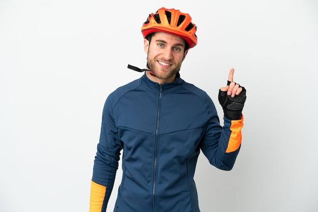 Homem jovem ciclista isolado no fundo branco mostrando e levantando um dedo em sinal dos melhores