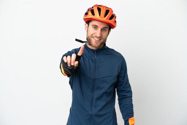 Homem jovem ciclista isolado no fundo branco, mostrando e levantando um dedo