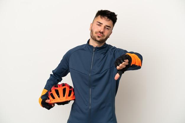 Homem jovem ciclista isolado no fundo branco, mostrando o polegar para baixo com expressão negativa