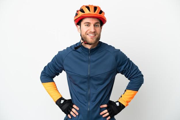 Homem jovem ciclista isolado no fundo branco, posando com os braços na cintura e sorrindo
