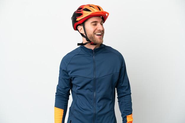 Homem jovem ciclista isolado no fundo branco rindo