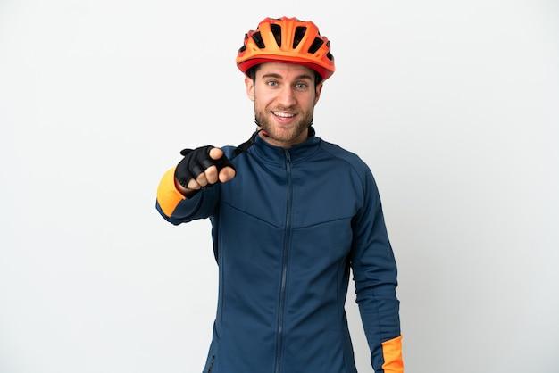 Homem jovem ciclista isolado no fundo branco surpreso e apontando para a frente