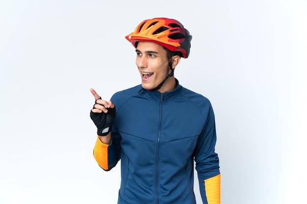 Homem jovem ciclista isolado no fundo com a intenção de descobrir a solução enquanto levanta um dedo