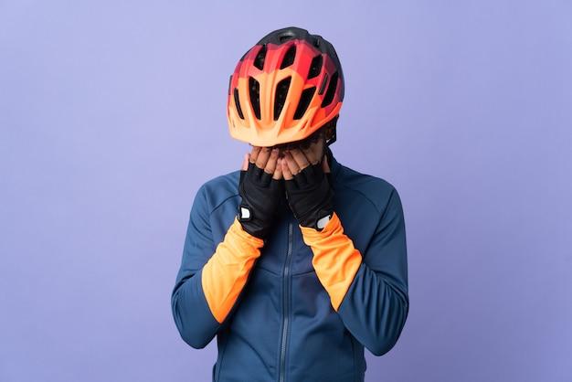 Homem jovem ciclista marroquino isolado em um fundo roxo com expressão cansada e doente