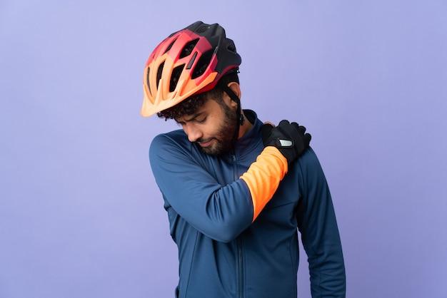 Homem jovem ciclista marroquino isolado em um fundo roxo, sofrendo de dores no ombro por ter feito um esforço