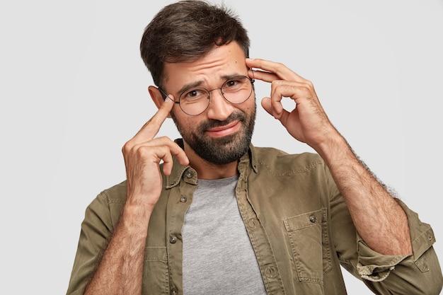 Homem jovem com a barba por fazer descontente mantém os dedos nas têmporas, franze a testa em desgosto, tenta se lembrar de algo, tem memória fraca, veste uma camisa da moda, posa contra a parede branca