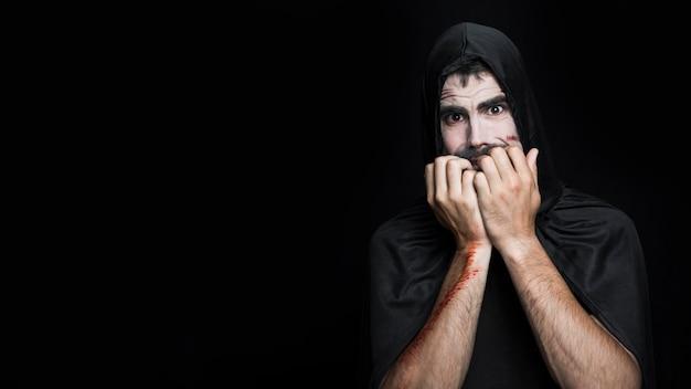 Homem jovem, com, assustado, rosto, em, traje halloween, posar, em, estúdio