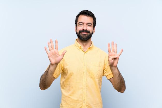 Homem jovem, com, barba, ligado, azul, contando nove, com, dedos