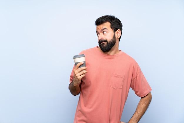 Homem jovem, com, barba, segurando, levar, café, isolado, azul, parede, fazendo, dúvida, gesto, olhar lado
