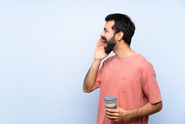 Homem jovem, com, barba, segurando, um, levar, café, sobre, isolado, azul, shouting, com, boca largo aberto