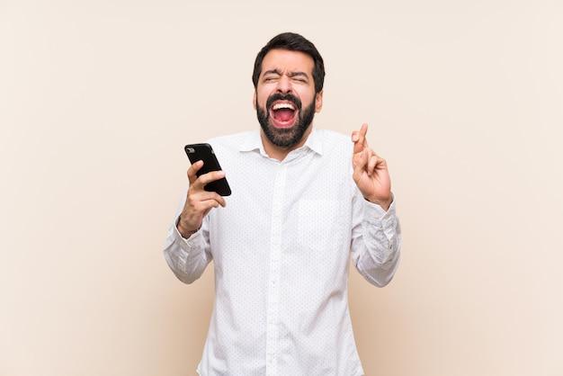 Homem jovem, com, barba, segurando, um, móvel, com, dedos cruzando