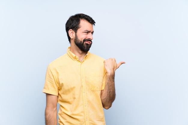Homem jovem, com, barba, sobre, isolado, azul, infeliz, e, apontar, ao lado