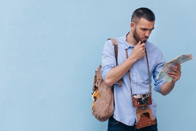 Homem jovem, com, câmera, ao redor, seu, pescoço, leitura, mapa, ligado, azul, fundo