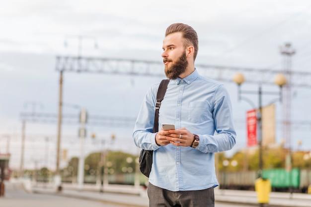 Homem jovem, com, cellphone, ficar, em, estação de comboios