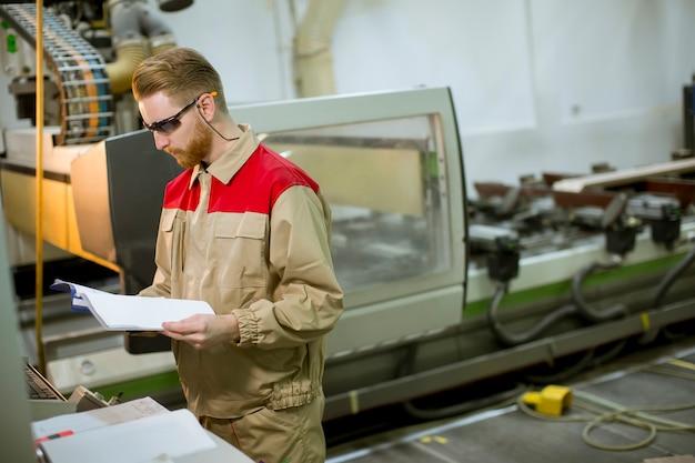 Homem jovem, com, desenhos técnicos, trabalhando, em, um, fábrica