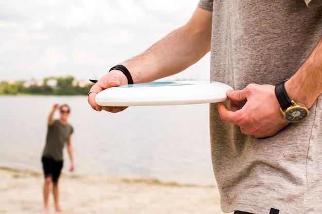 Homem jovem, com, frisbee, prato, ligado, praia