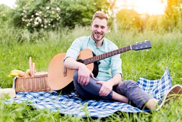 Homem jovem, com, guitarra, ligado, piquenique