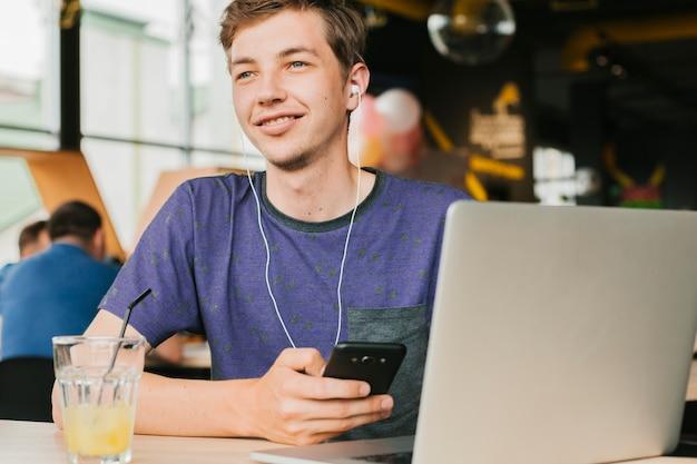 Homem jovem, com, laptop, e, fones