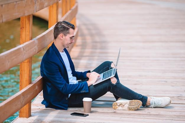 Homem jovem, com, laptop, trabalhando, ao ar livre, parque