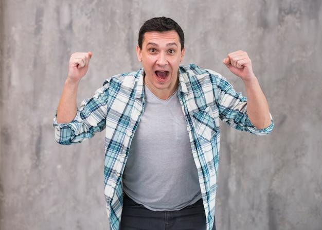 Homem jovem, com, levantando mãos, gritando, câmera