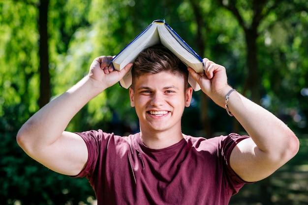 Homem jovem, com, livro, ligado, cabeça