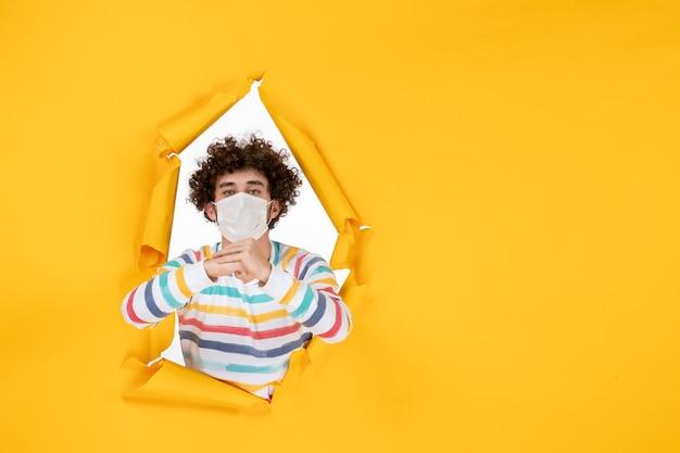 Homem jovem com máscara estéril em frente a frente com vírus covidêmico da foto colorida da saúde amarelo - vírus pandêmico humano