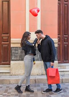 Homem jovem, com, pacotes, beijando, mão, de, mulher, e, voando, balloon