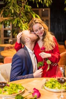 Homem jovem, com, rosa, beijando, mulher, ligado, bochecha