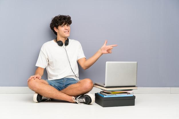 Homem jovem, com, seu, laptop, sentando, um, a, chão, apontar dedo, para, a, lado