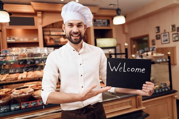 Homem jovem, com, sinal bem-vindo, ficar, em, padaria