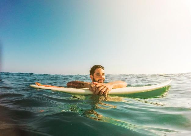 Homem jovem, com, surfboard, em, azul, água