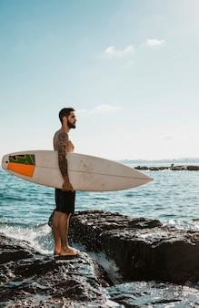 Homem jovem, com, tábua surf, ligado, rocha, perto, água