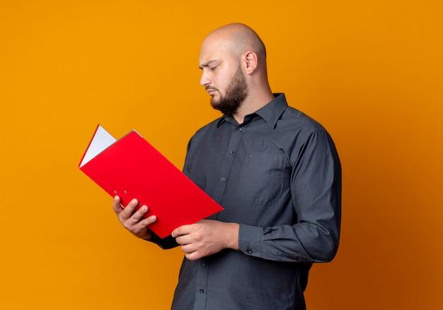 Homem jovem concentrado e careca de call center segurando e olhando para uma pasta isolada em laranja com espaço de cópia