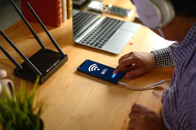 Homem jovem, conectando, roteador, wi-fi, ligado, smartphone, para, internet, e, social, mídia