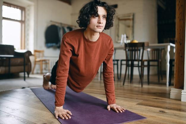 Homem jovem confiante autodeterminado com cabelo encaracolado, fazendo a prancha na esteira de fitness durante o treinamento matinal em casa por causa do distanciamento social.