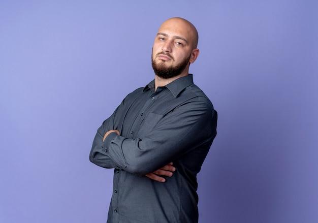 Homem jovem confiante e careca de call center em pé com a postura fechada em vista de perfil, isolado em roxo com espaço de cópia