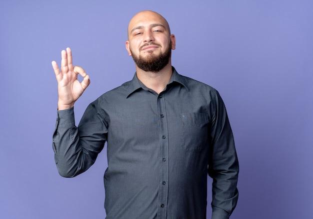 Homem jovem confiante e careca de call center fazendo sinal de ok isolado em roxo com espaço de cópia
