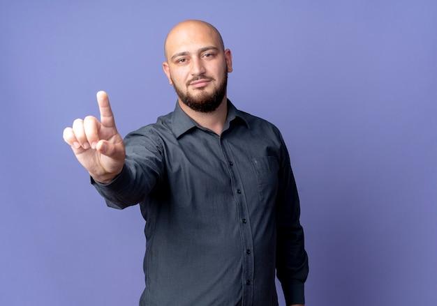 Homem jovem confiante e careca de call center levantando o dedo isolado em roxo com espaço de cópia