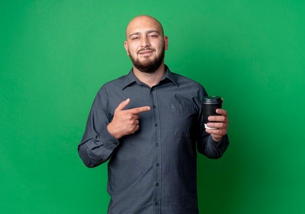 Homem jovem confiante e careca de call center segurando e apontando para uma xícara de café de plástico isolada em verde com espaço de cópia