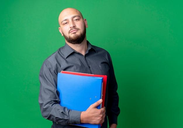 Homem jovem confiante e careca no call center segurando pastas isoladas em verde com espaço de cópia