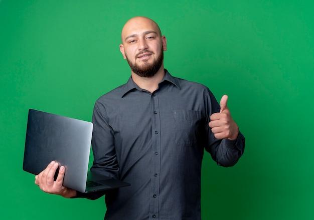 Homem jovem confiante e careca no call center segurando um laptop e mostrando o polegar isolado no verde com espaço de cópia