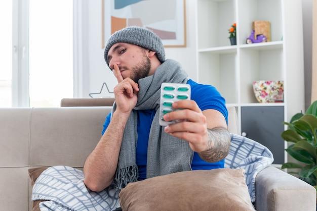 Homem jovem confiante e doente com cachecol e chapéu de inverno, sentado no sofá na sala de estar com o travesseiro nas pernas esticando o pacote de cápsulas fazendo gesto de silêncio