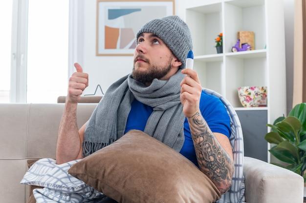 Homem jovem confiante e doente com cachecol e chapéu de inverno, sentado no sofá na sala de estar com o travesseiro nas pernas, segurando o termômetro, olhando para cima, mostrando o polegar
